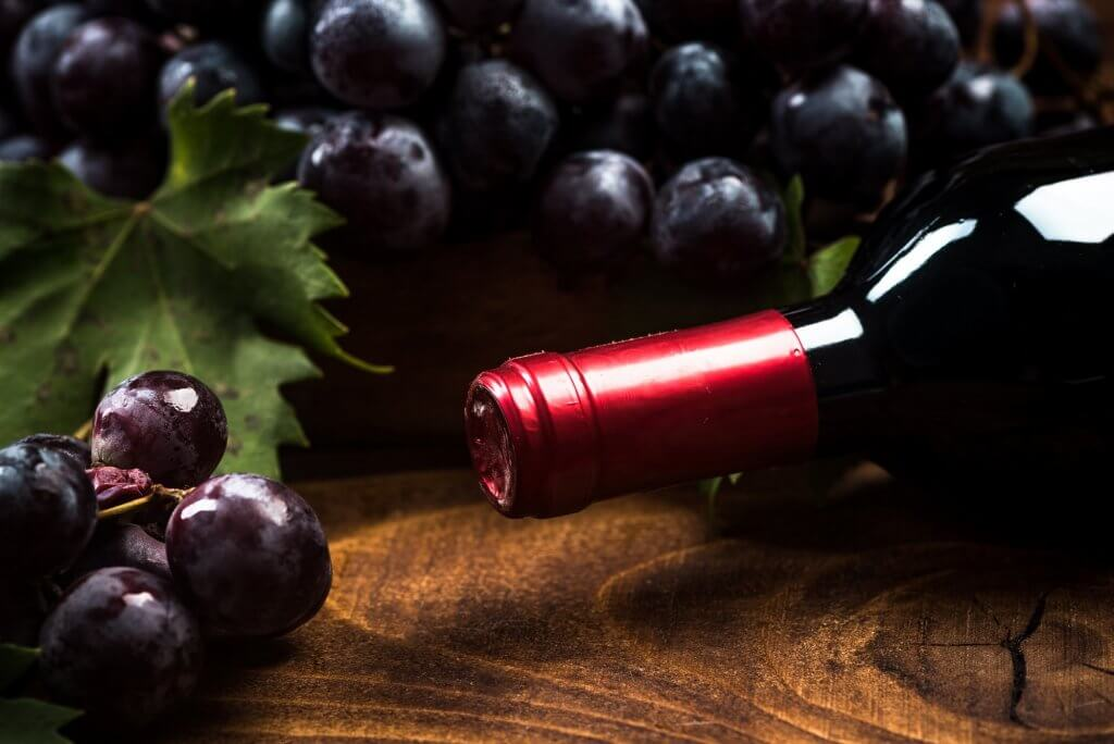 Bottle of red wine and fresh vine grapes